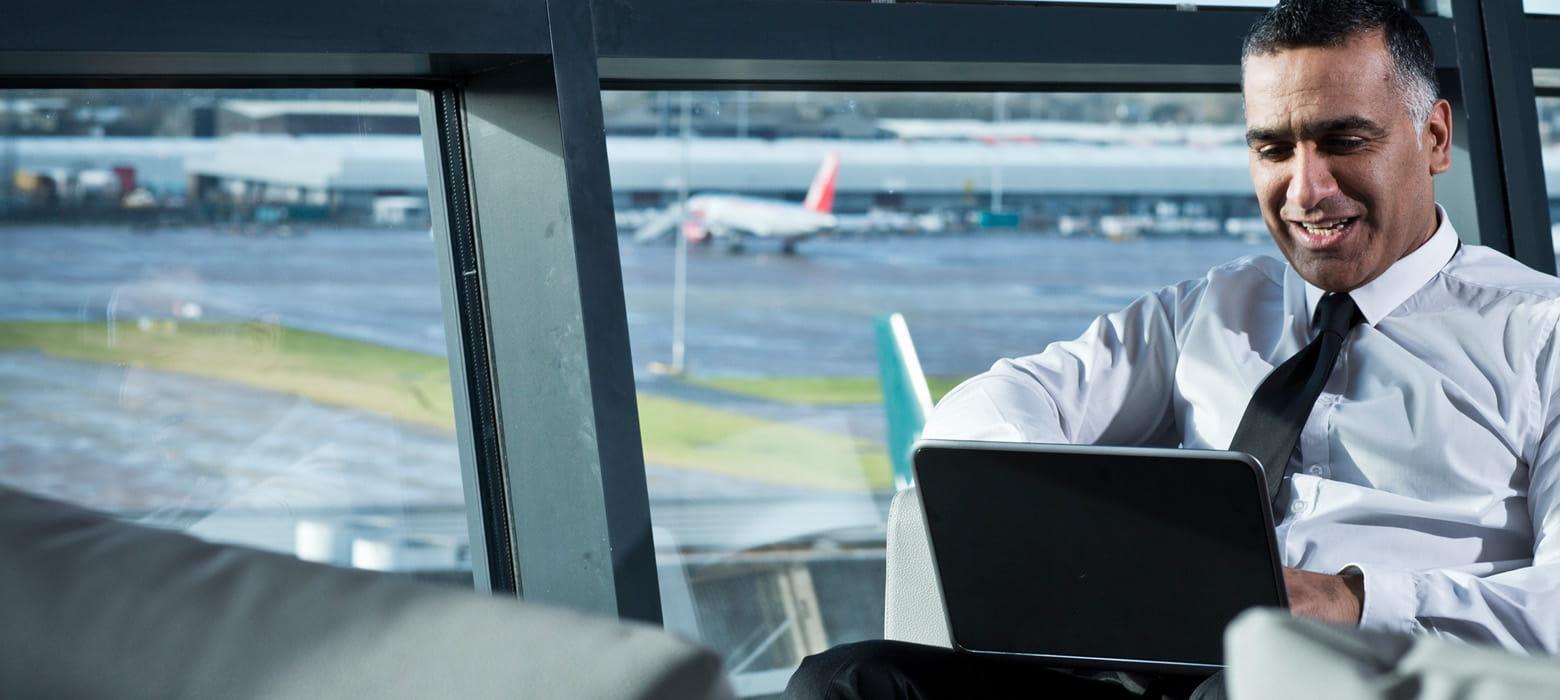 Mies tarkistaa lentokentällä aikansa kuluksi miten yrityksen tulostimen toimivat konttorilla