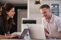 Mies ja nainen työpisteessään tulostin taustalla