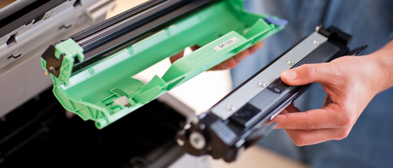 Mies vaihtaa alkuperäistä Brother-värikasettia tulostimeensa