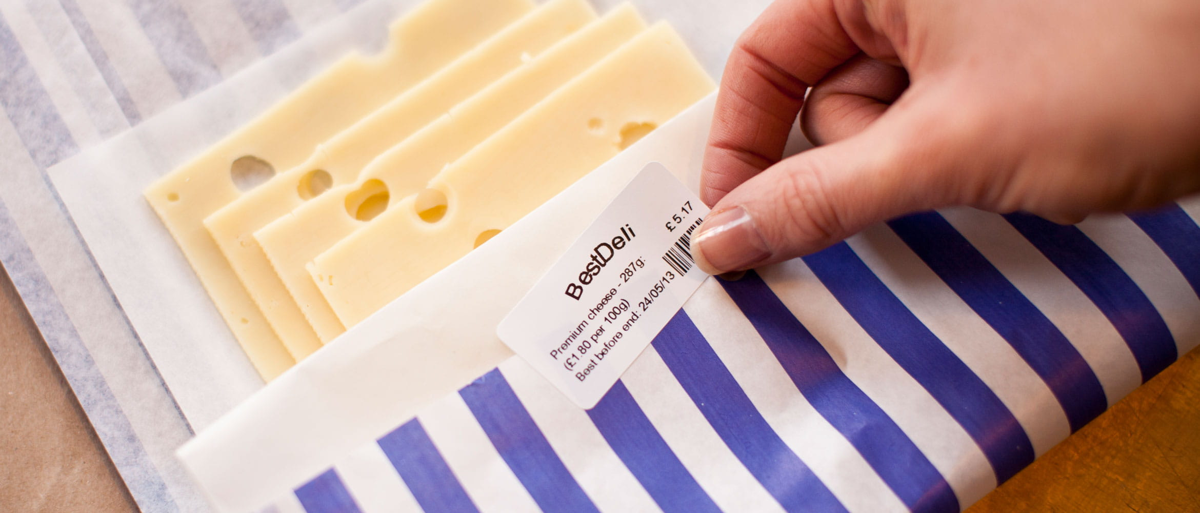Close up of label being stuck on to some cheese packaging