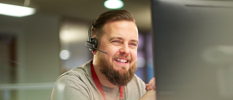 Hymyilevä mies opastaa asiakkaita