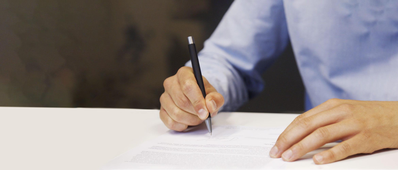 Mies allekirjoittaa sopimusta sinisessä paidassaan