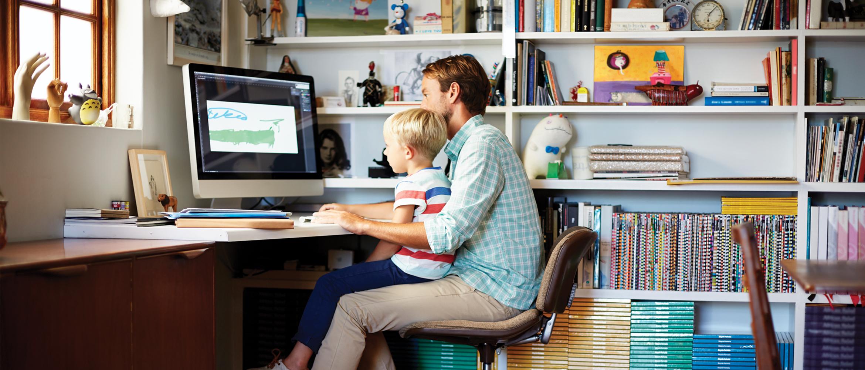 Isä ja lapsi istuvat työpöydän ääressä