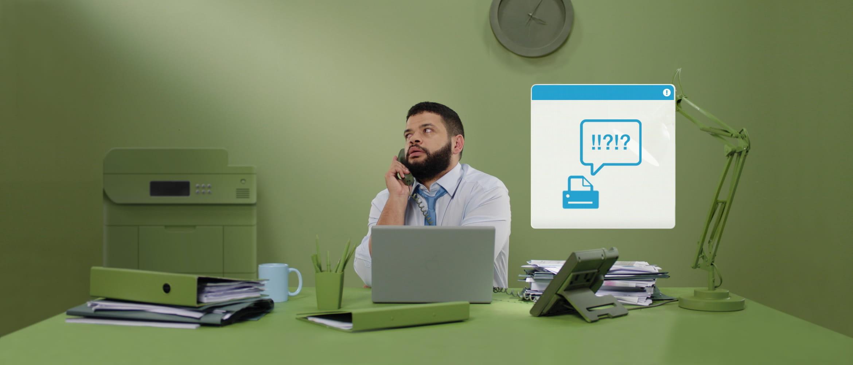Mies istuu toimistossaan ja puhuu puhelimessa