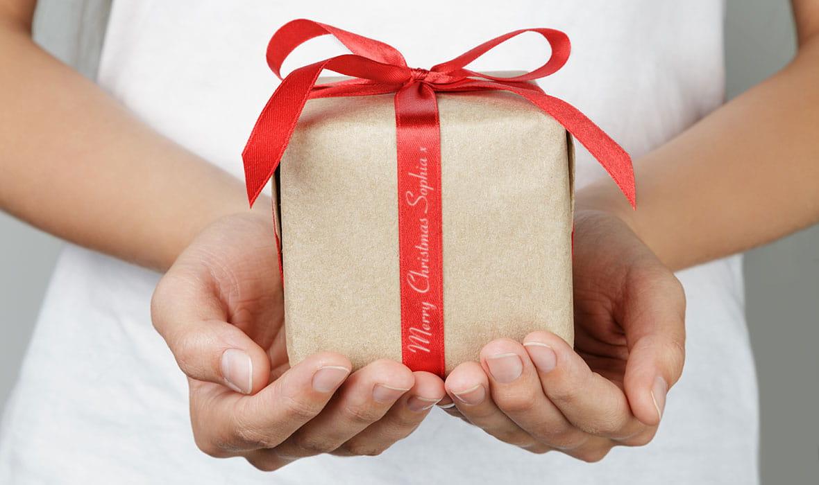 Punaiseen satiininauhaan kääritty tyylikäs joulupaketti sisältää viestin lahjansaajalle
