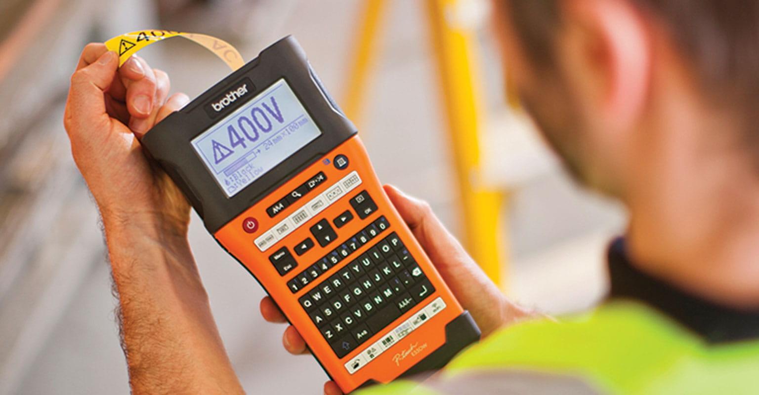 Sähkömies käyttää PT-E550WSP-tarratulostinta