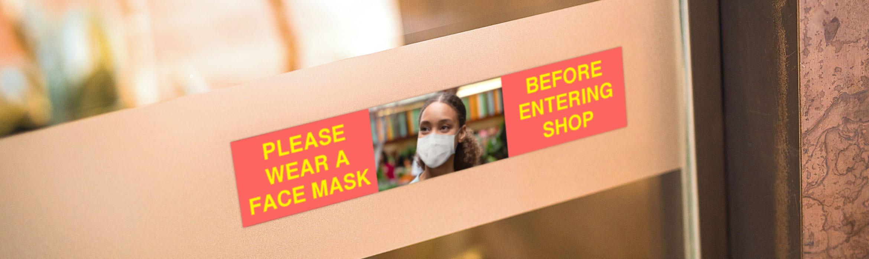 Värikäs kuvallinen opaste muistuttaa asiakkaita käyttämään maskia