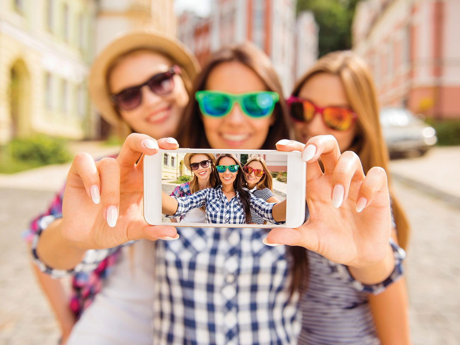 Kolme tyttöä ottaa selfie-kuvaa IPhonella
