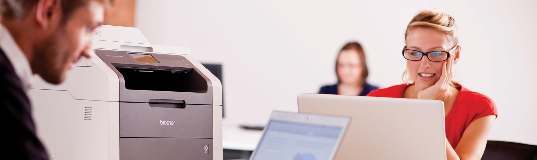 Nainen työskentelee läppärillään Brother-tulostin vieressä käyttövalmiina