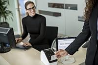 Nainen poimii tarraa QL-810W tulostimesta