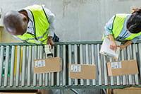 Työntekijät tarkastavat tarroin merkittyjä laatikoita