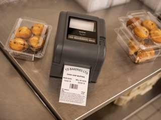 Brotherin TD-4T-tarratulostin leipomon pöydällä leivonnaisten vieressä