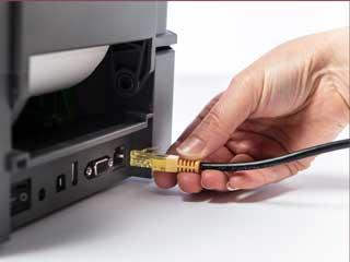 Verkkokaapeli kiinnitetään tarratulostimen takana olevaan porttiin