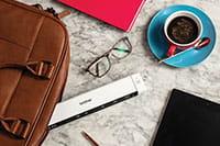 Pöydällä silmälasit, kahvikuppi, kynä, mobiiliskanneri, tabletti, pinkki muistikirja ja nahkainen läppärilaukku