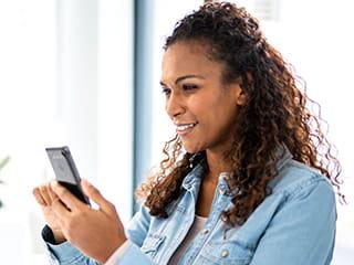 Nainen valitsee puhelimestaan Bluetooth-yhteyden välityksellä P-touch CUBE Plus Home -tarratulostimen