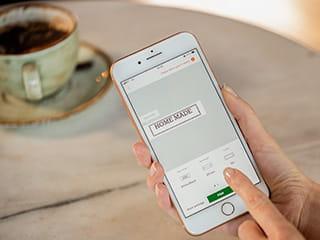 Nainen suunnittelee tarramerkintäänsä kahvilassa Design&Print -appsilla