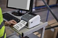 Mies tulostaa tietokoneesta tarraa varaston TD-4D-tulostimeen