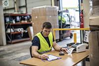 Mies tulostaa varastossa lähetetarraa TD-4D-malliston etikettitulostimella