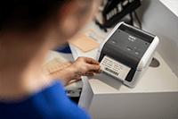 Hoitaja tulostaa potilastarraa TD4420DN-tulostimella