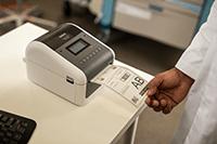 Lääkäri poimii tarratulostetta Brother TD4550DNWB-tulostimesta