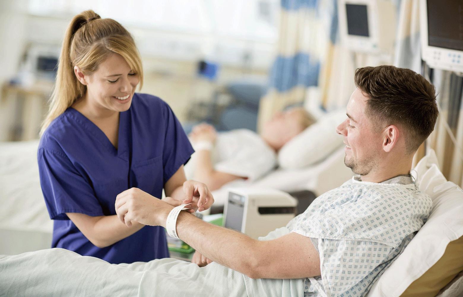 Sairaanhoitaja kiinnittää Brotherin tulostimella tulostettua potilasranneketta
