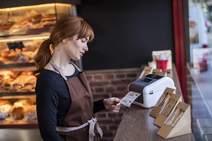 Nainen käyttää TD4-tulostinta leipomossa