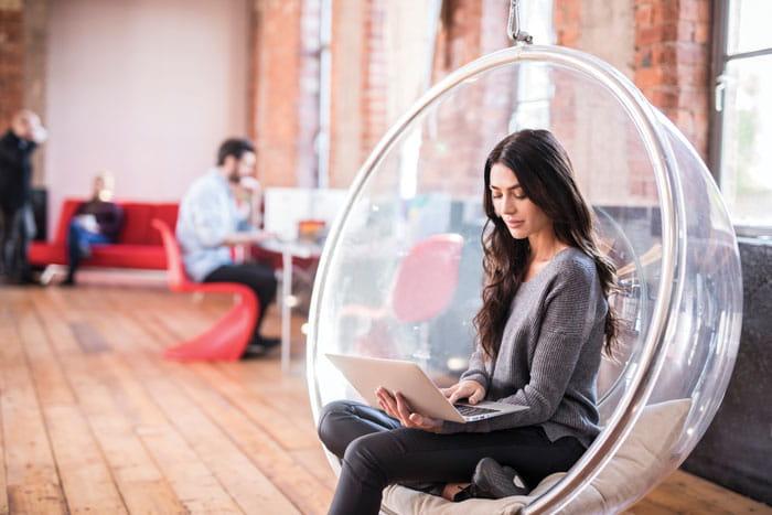Nainen istuu läpinäkyvässä tuolissa kannettavaa tietokonetta käyttäen