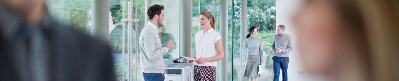 Mies ja nainen juttelevat Brother-tulostimen vieressä